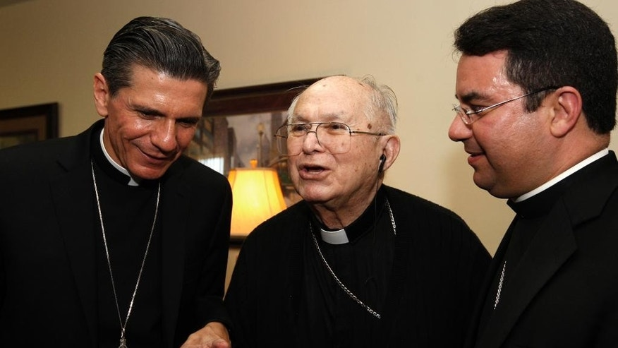 FILE - In this Oct. 14, 2010, file photo, the Most Rev. Archbishop Gustavo Garcia-Siller, left, and Bishop Oscar Cantu, right, listen as Archbishop Emeritus Patricio Flores, center, talks with them at Padua Place in San Antonio. Flores has died at the age of 87. In a lengthy statement, the San Antonio archdiocese said Flores died Monday, Jan. 9, 2017, of pneumonia and congestive heart failure at a San Antonio assisted living center for retired priests. (Jerry Lara/The San Antonio Express-News via AP, File)