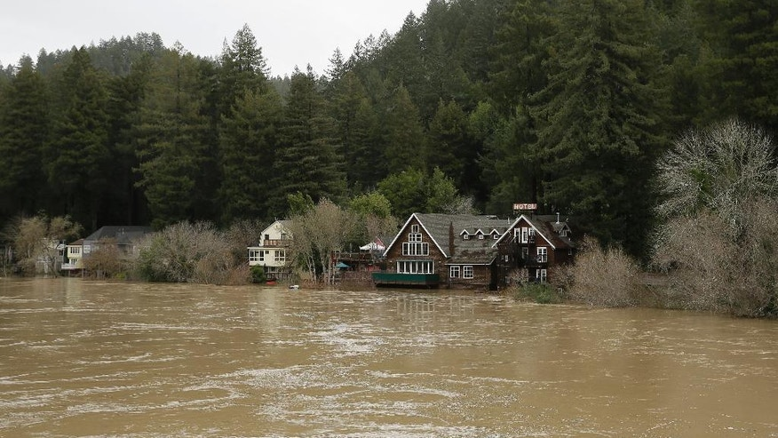 The Russian River flows just below cabins and a hotel Monday, Jan. 9, 2017, in Monte Rio, Calif. A massive storm system stretching from California into Nevada lifted rivers climbing out of their banks, flooded vineyards and forced people to evacuate after warnings that hillsides parched by wildfires could give way to mudslides. (AP Photo/Eric Risberg)