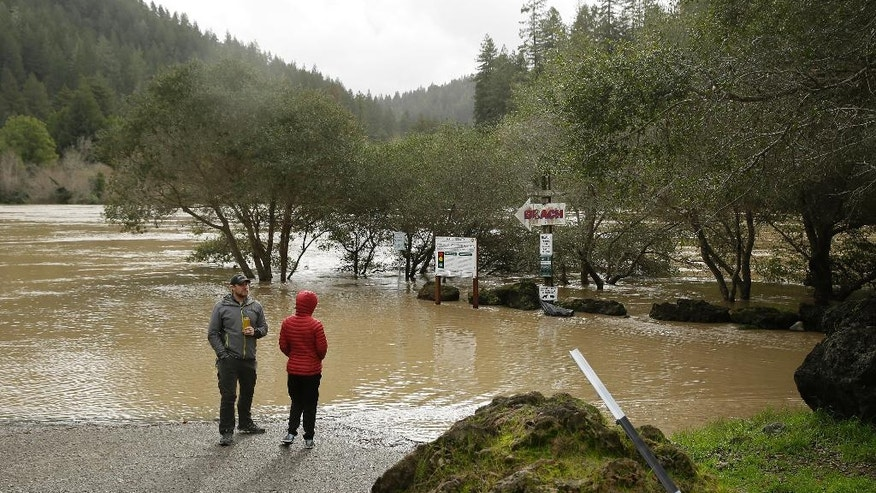 A couple looks out at the Russian River as it flows through a beach park Monday, Jan. 9, 2017, in Monte Rio, Calif. A massive storm system stretching from California into Nevada lifted rivers climbing out of their banks, flooded vineyards and forced people to evacuate after warnings that hillsides parched by wildfires could give way to mudslides. (AP Photo/Eric Risberg)