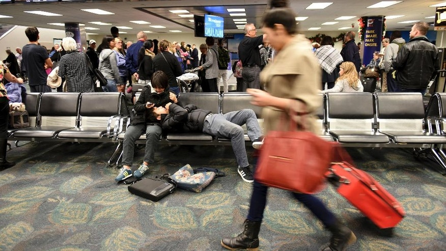Air Canada passengers pick up their luggage at the partially opened Terminal 2 at Fort Lauderdale-Hollywood International Airport Sunday, Jan. 8, 2017.  A gunman opened fire Friday in a baggage claim area at the Fort Lauderdale international airport, killing five people and wounding eight before he was taken into custody. (Taimy Alvarez/South Florida Sun-Sentinel via AP)