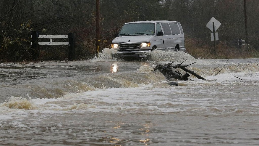 A van drives through flooded water on Green Valley Road in Graton, Calif., Saturday, Jan. 7, 2017. On the California coast, weather forecasters anticipate a storm surge from the Pacific called an atmospheric river to dump several inches of rain from Sonoma to Monterey counties, and up to a foot in isolated places in the Santa Cruz mountains. (AP Photo/Jeff Chiu)