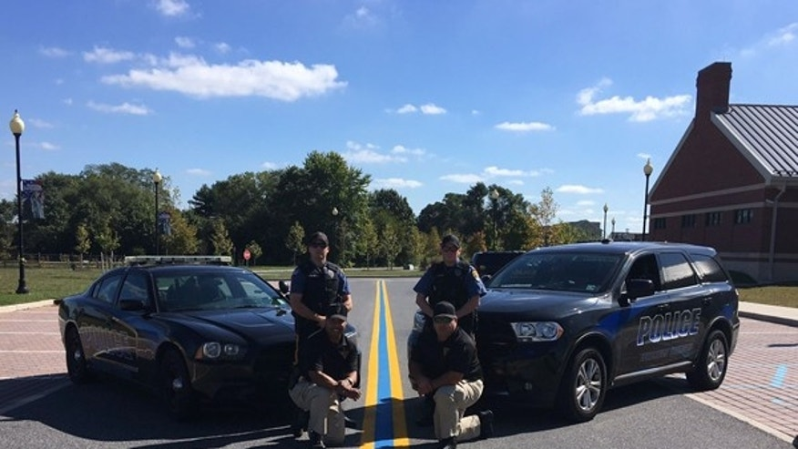 Police officers in Woolwich Twp., NJ pose with a blue line tribute painted last October.