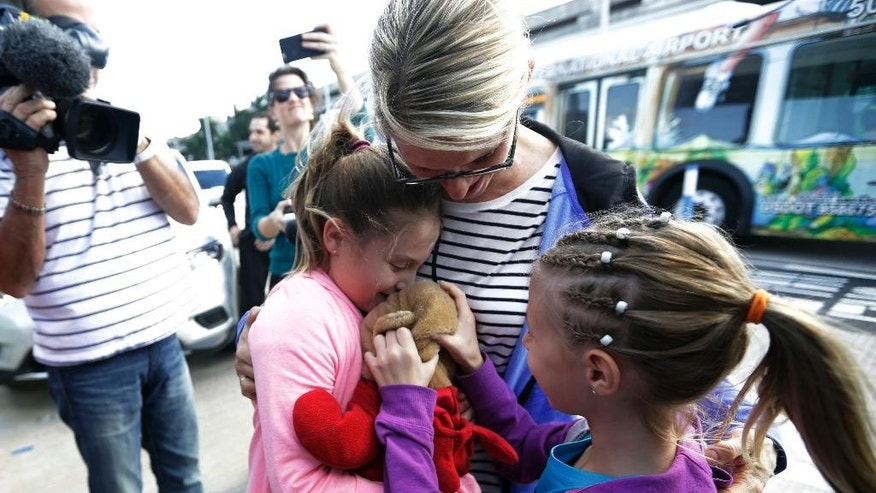 Courtney Gelinas, left, is hugged by her mother Kim Lariviere, center, after being reunited with her stuffed bear Rufus, at the Fort Lauderdale-Hollywood International Airport, Tuesday, Jan. 10, 2017, in Fort Lauderdale, Fla. Gelinas, of Windsor, Ontario, Canada, was traveling home with her family after a Caribbean cruise. They became separated from their belongings as they fled during last week's shooting at the airport in which five people were killed. At right is Kim's sister Kacie Galinas. (AP Photo/Lynne Sladky)