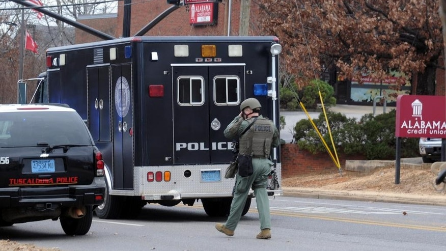 Law enforcement surround the Alabama Credit Union on reports of a hostage standoff in Tuscaloosa, Ala., Tuesday, Jan. 10, 2017.  Lt. Teena Richardson, a Tuscaloosa police spokeswoman, told al.com that a gunman entered the building and took the employees inside hostage.    (Ben Flanagan/AL.com via AP)