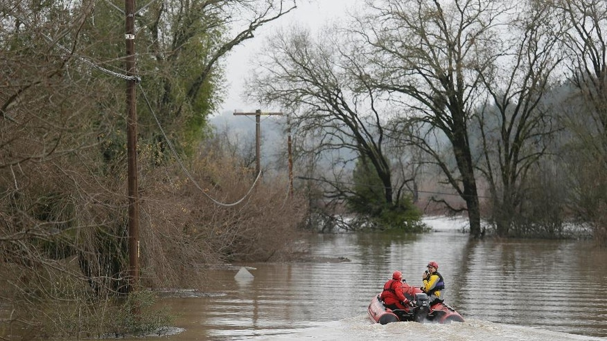 Fire department members head out on a rescue mission down flooded Wohler Road, Monday, Jan. 9, 2017, in Forestville, Calif. A massive storm system stretching from California into Nevada lifted rivers climbing out of their banks, flooded vineyards and forced people to evacuate after warnings that hillsides parched by wildfires could give way to mudslides. (AP Photo/Eric Risberg)