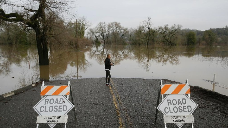 Michelle Wolfe, who had to evacuate her nearby mobile home, looks out toward flooded vineyards in the Russian River Valley, Monday, Jan. 9, 2017, in Forestville, Calif. A massive storm system stretching from California into Nevada lifted rivers climbing out of their banks, flooded vineyards and forced people to evacuate after warnings that hillsides parched by wildfires could give way to mudslides. (AP Photo/Eric Risberg)