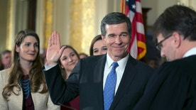 Roy Cooper is ceremonially sworn in as Governor of North Carolina by Chief Justice Mark Martin during a ceremony on Friday, Jan. 6, 2017 at the Executive Mansion in Raleigh, N.C. Cooper's daughters from left, Hilary, Natalie and Claire look on. The swearing in ceremony, originally scheduled for Saturday, was cancelled and moved to Friday due to a winter storm that is expected to move through Raleigh overnight. (Robert Willett/The News & Observer via AP) /The News & Observer via AP)
