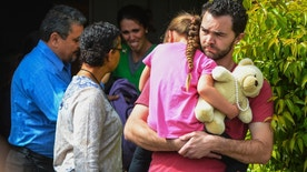 Rusty Page carries Lexi while Summer Page, in the background, cries as members of family services, left, arrive to take Lexi away from her foster family in Santa Clarita, Calif., Monday, March 21, 2016. Lexi, who spent most of her life with California foster parents, was removed from her home on Monday under a court order that concluded her native American blood requires her placement with relatives in Utah. (David Crane/Los Angeles Daily News via AP) MANDATORY CREDIT