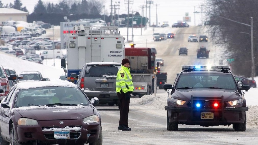 A Minnesota State Trooper directs traffic on East Highway Street in front of McNeilus Truck and Manufacturing after a possible explosion Wednesday, Jan. 11, 2017, in Dodge Center, Minn. (Andrew Link/Rochester Post Bulletin via AP)