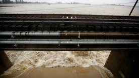Water from the Sacramento River flows through one of the gates of the Sacramento Weir, Tuesday, Jan. 10, 2017, in West Sacramento, Calif. State officials opened the Sacramento Weir gates for the first time in more than a decade as stormy weather continues to lash Northern California and Nevada. (AP Photo/Rich Pedroncelli)
