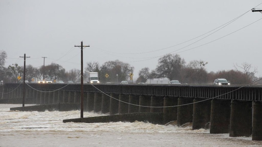 Water from the Sacramento River flows through some of the gates of the Sacramento Weir, Tuesday, Jan. 10, 2017, in West Sacramento, Calif. State officials opened the Sacramento Weir gates for the first time in more than a decade as stormy weather continues to lash Northern California and Nevada. (AP Photo/Rich Pedroncelli)