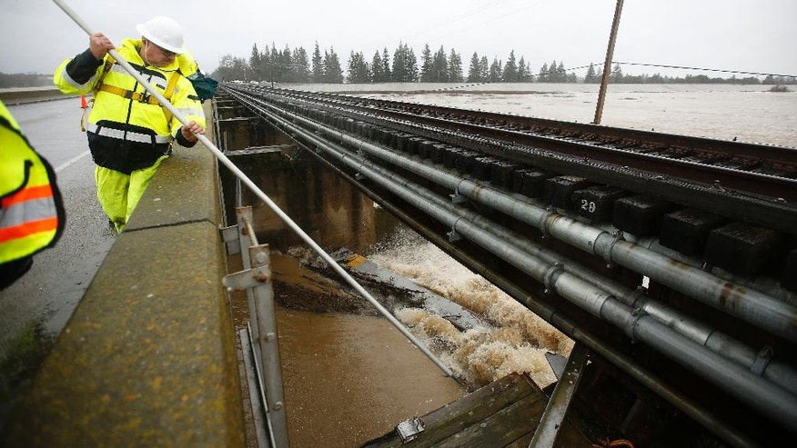 A worker from the Department of Water Resources opens one of the flood gates of the Sacramento Weir, Tuesday, Jan. 10, 2017, in West Sacramento, Calif. State officials opened the Sacramento Weir gates for the first time in more than a decade as stormy weather continues to lash Northern California and Nevada. (AP Photo/Rich Pedroncelli)