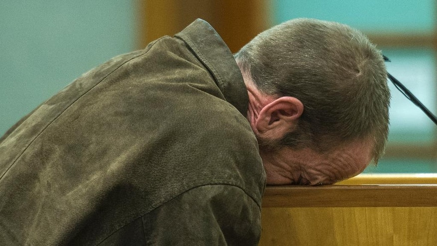 In this Tuesday, Jan. 10, 2017 photo, Kenneth Lee Drew puts his face on the lectern during his sentencing at 4th District Court in American Fork, Utah. Drew, a Utah repossession agent accused of forcing a woman off the road, leading to a fatal crash, while trying to take back her car was sentenced Tuesday, to one to 15 years in prison, after pleading guilty to manslaughter. (Chris Detrick/The Salt Lake Tribune, via AP, Pool)