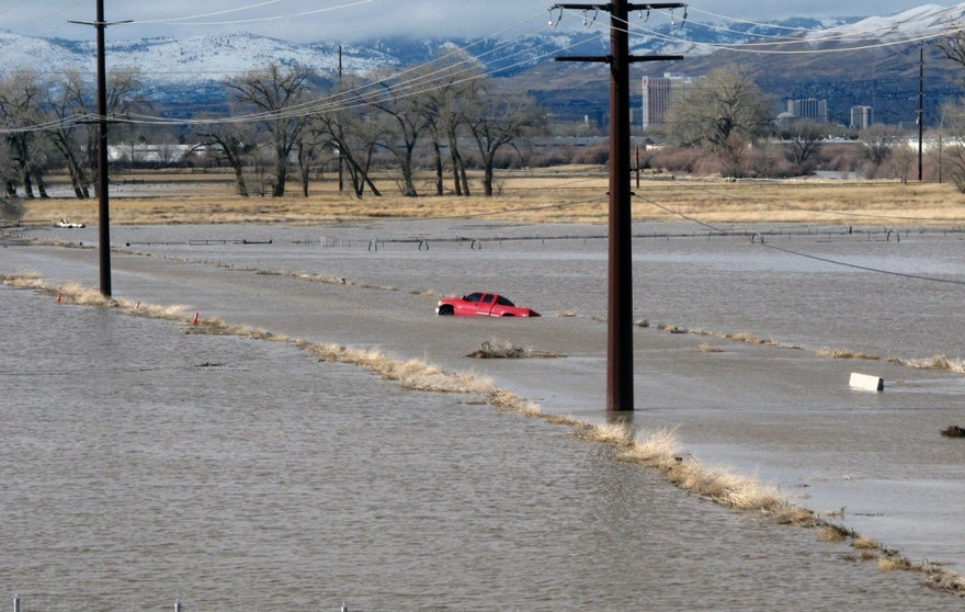 A red pickup truck sits abandoned it after it got stuck in floodwaters Monday, Jan. 9, 2017, on a closed road at a University of Nevada, Reno, research farm bordering the Truckee River south of U.S. Interstate 80. (AP Photo/Scott Sonner).