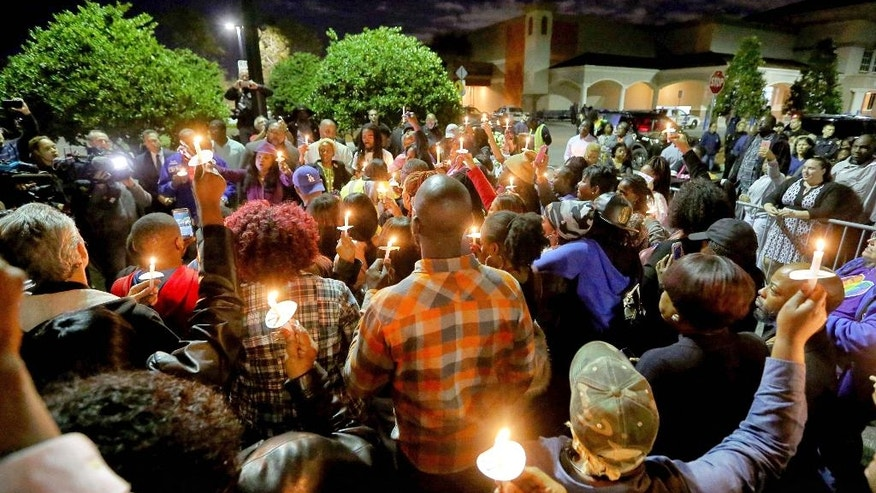 Candles and TV lights illuminate the crowd during a vigil at Wal-Mart store where an Orlando police sergeant was killed Monday and for an Orange County Sheriff's Office deputy killed during a manhunt of the suspect, in Orlando, Fla., Tuesday, Jan. 10, 2017. (Joe Burbank/Orlando Sentinel via AP)