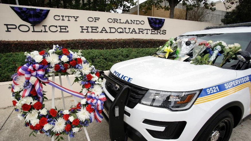 A wreath and flowers surround Orlando police shooting victim, officer Debra Clayton's patrol car, in front of police headquarters, Tuesday, Jan. 10, 2017, in Orlando, Fla. Clayton was killed Monday, and a manhunt continues as law enforcement officials search for the suspect. (AP Photo/John Raoux)