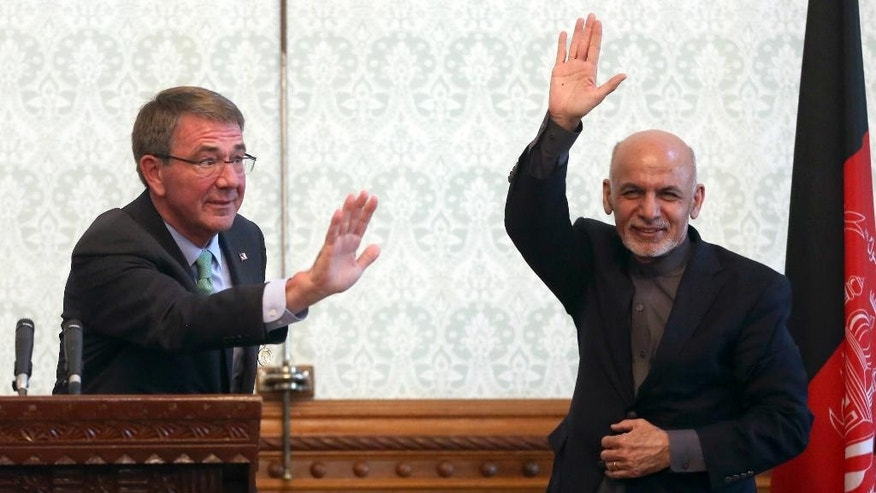 FILE -- In this Dec. 9, 2016 file photo, Afghan President Ashraf Ghani, right, and U.S. Defense Secretary Ash Carter, left, wave after a press conference at presidential palace in Kabul, Afghanistan. A U.S. report released Wednesday, Jan. 11, 2017, said that Afghanistan needs a stable security environment to prevent it from again becoming a safe haven for al-Qaida and other militants. The new report by the Special Inspector General for Afghanistan Reconstruction says Afghan security forces have not yet become capable of securing all of Afghanistan by themselves. (AP Photos/Massoud Hossaini, File)