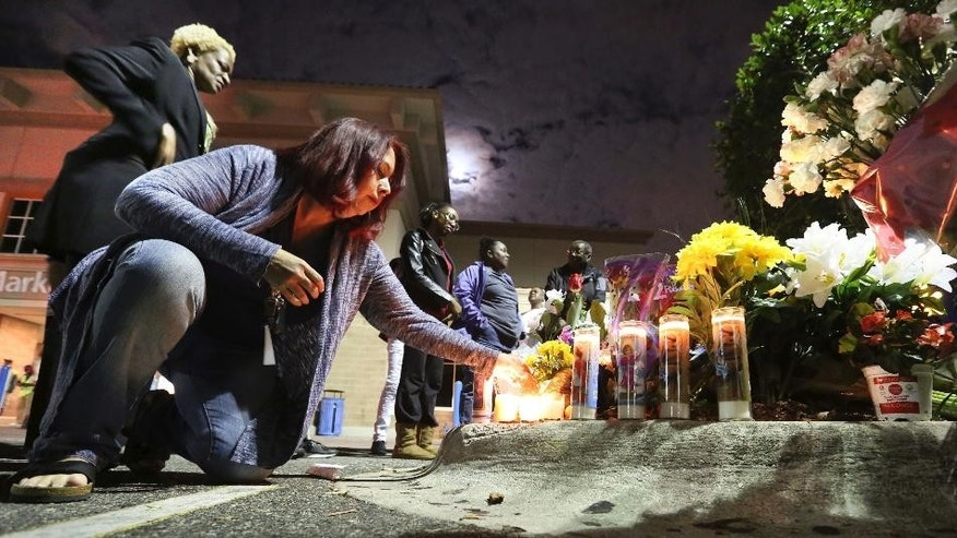 Tricia Dennis and Orlando city commissioner Regina Hill, far left, pay their respects at a makeshift memorial to honor an Orlando police sergeant killed Monday at the parking lot of a Wal-Mart store and an Orange County Sheriff's Office deputy before a candlelight vigil at the store in Orlando, Fla., Tuesday, Jan. 10, 2017. (Joe Burbank/Orlando Sentinel via AP)