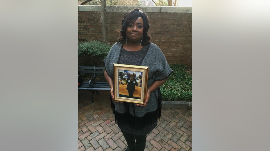 Rose Simmons, the daughter of Rev. Daniel Simmons, Sr., poses with a photograph of her father outside of U.S. District Court in Charleston, S.C., Wednesday, Jan. 11, 2017, hours after Judge Richard Gergel formally confirmed jurors on Tuesday sentenced Dylann Roof to death. Simmons said Roof killed her father and eight others at Emanuel AME Church on June 17, 2015. (AP Photo/Alex Sanz)