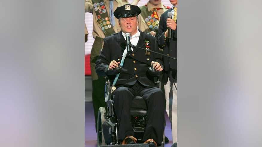FILE- In this Aug. 30, 2004 file photo, New York Police Officer Steven McDonald recites the Pledge of Allegiance before the morning session of the Republican National Convention at Madison Square Garden in New York. On Tuesday, Jan. 10, 2017, officials said McDonald, who was paralyzed by a bullet and became an international voice for peace after he publicly forgave the gunman, died at the age of 59. (AP Photo/J. Scott Applewhite, File)