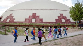 FILE - In this Sept. 25, 2014 file photo, students walk between buildings at the Little Singer Community School in Birdsprings, Ariz., on the Navajo Nation. A federal lawsuit filed Thursday, Jan. 12, 2017, says U.S. Bureau of Indian Education schools are chronically understaffed, lack systems to provide special education and have a deficient curriculum. A coalition of advocacy groups announced the lawsuit involving Havasupai students at a northern Arizona school inside the Grand Canyon, but which could affect other BIE schools. (AP Photo/John Locher, File)