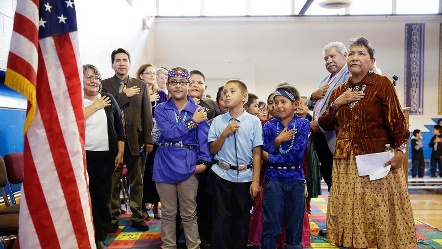 "FILE - In this Sept. 26, 2014 file photo, students and faculty recite the ""Pledge of Allegiance"" during an assembly at the Crystal Boarding School in Crystal, N.M., on the Navajo Nation. A federal lawsuit filed Thursday, Jan. 12, 2017, says U.S. Bureau of Indian Education schools are chronically understaffed, lack systems to provide special education and have a deficient curriculum. A coalition of advocacy groups announced the lawsuit involving Havasupai students at a northern Arizona school inside the Grand Canyon, but which could affect other BIE schools. (AP Photo/John Locher, File)"