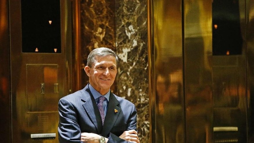 FILE - In this Dec. 12, 2016 file photo, National Security Adviser-designate Michael T. Flynn waits for an elevator in the lobby at Trump Tower in New York. The Obama administration is aware of frequent contacts between President-elect Donald Trump's top national security adviser Michael Flynn and Russia's ambassador to the United States, including on the day President Barack Obama hit Moscow with sanctions in retaliation for election-related hacking, a senior U.S. official said Friday, Jan. 13, 2017.  (AP Photo/Kathy Willens, File)