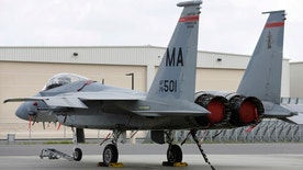 FILE - In this Aug. 27, 2014, file photo, a Massachusetts Air National Guard F-15C fighter aircraft sits near a hangar at Barnes Air National Guard Base, in Westfield, Mass. A 14-year-old Air National Guard proposal could be considered in 2017 that would allow the twin-engine fighters from Massachusetts to fly as low as 500 feet along a corridor in western Maine and the northern tip of New Hampshire. (AP Photo/Steven Senne, File)
