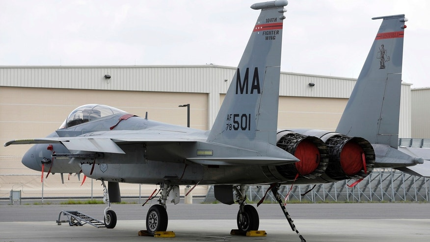 In this Aug. 27, 2014, file photo, a Massachusetts Air National Guard F-15C fighter aircraft sits near a hangar at Barnes Air National Guard Base, in Westfield, Mass