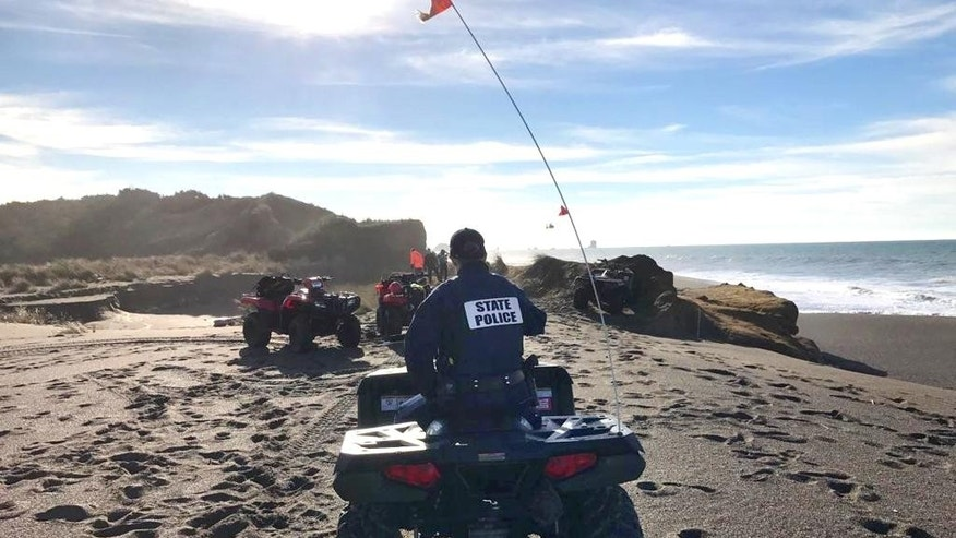 In this photo provided by the Oregon State Police taken Sunday, Jan. 15, 2017, OSP troopers on all-terrain vehicles search a beach about two miles north of Cape Blanco, Oregon, where a father and his young son were swept out to sea Sunday as they walked near the surf. (Oregon State Police via AP)