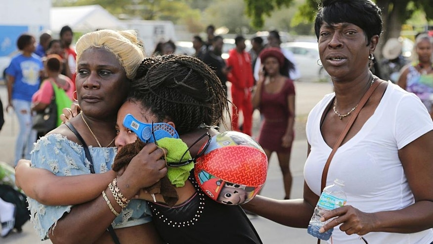 People react after several were injured in a shooting at Martin Luther King Jr. Memorial Park in Miami-Dade, Fla., Monday, Jan. 16, 2017. The Miami Herald reports that hundreds of people had gathered in the park after the annual MLK Day parade. (Carl Juste/Miami Herald via AP)