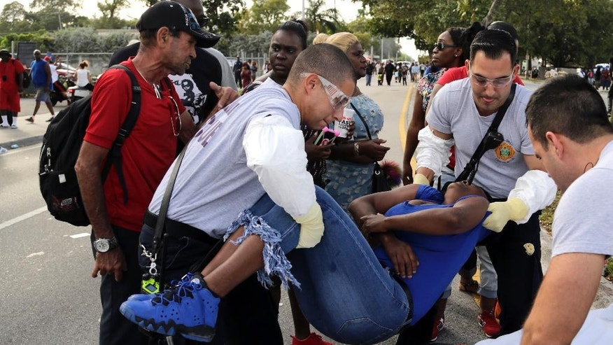 Miami-Dade Fire and Rescue paramedics lift a woman after she lost consciousness after several were injured in a shooting at Martin Luther King Jr. Memorial Park in Miami-Dade, Fla., Monday, Jan. 16, 2017. The Miami Herald reports that hundreds of people had gathered in the park after the annual MLK Day parade. (Carl Juste/Miami Herald via AP)