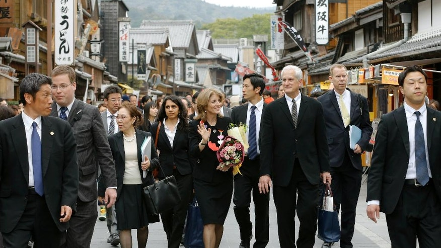 FILE - In this April 16, 2014, file photo, U.S. Ambassador to Japan Caroline Kennedy, center, and her husband Edwin Arthur Schlossberg, center right, walk on a souvenir shopping street, outside of Ise Grand Shrine in Ise, Mie Prefecture, Japa. Kennedy is stepping down Wednesday, Jan. 18, 2017 after three years as U.S. ambassador to Japan, where she was welcomed like a celebrity and worked to deepen the U.S.-Japan relationship despite regular flare-ups over American military bases on the southern island of Okinawa. (AP Photo/Shizuo Kambayashi, File)