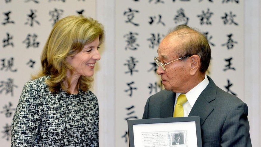 FILE- In this Feb. 12, 2014, file photo, U.S. Ambassador to Japan Caroline Kennedy, left, shakes hands with Okinawa Gov. Hirokazu Nakaima after she handed a copy of visa application form of her father President John F. Kennedy, which was issued when he visited Japan, at Okinawa Prefectural Government in Naha, Okinawa. Kennedy is stepping down Wednesday, Jan. 18, 2017 after three years as U.S. ambassador to Japan, where she was welcomed like a celebrity and worked to deepen the U.S.-Japan relationship despite regular flare-ups over American military bases on the southern island of Okinawa. (Kyodo News via AP, File)