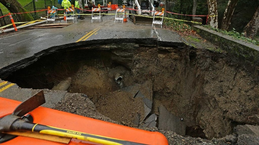 Contractors survey a 72-inch sinkhole Wednesday, Jan. 18, 2017, in Orinda, Calif. The city council of Orinda declared a State of Emergency Tuesday night because of a large sinkhole caused by last week's wet weather. Repairs will take at least four weeks, as the San Francisco Bay Area is being hit with a new series of rain storms. (AP Photo/Ben Margot)