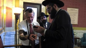 Rabbi Berry Nash, right, prays as Montana Rep. Dave Fern, R-Whitefish, wears boxes containing Torah versus called Tefillin on Wednesday, Jan. 18, 2017 in Helena, Mont. Nash was among a delegation of Orthodox Jewish rabbis from the U.S. and Canada who met with Fern and other state leaders to thank them for defending the Jewish community in Whitefish when it was threatened and harassed by white supremacists last month. (AP Photo/Matt Volz).