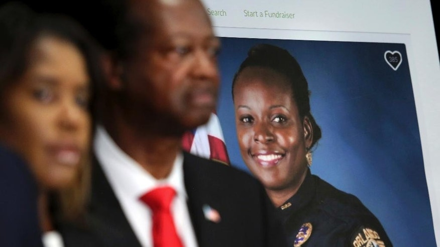 A GoFundMe poster for slain Orlando Police Lt. Debra Clayton is seen during a news press conference at the Orlando Police headquarters in Orlando, Fla., Tuesday, Jan. 17, 2017. Markeith Loyd, the suspect in the fatal shooting of Clayton, was captured Tuesday night after eluding a massive manhunt for more than a week, authorities said. (Joe Burbank/Orlando Sentinel via AP)