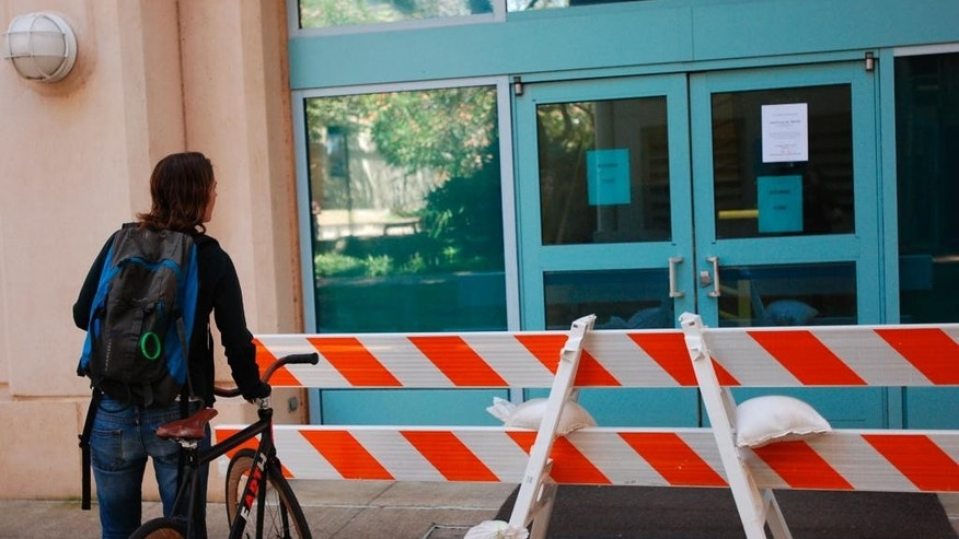 FILE - This March 17, 2016 photo shows a woman reading a sign informing people a building is closed on the University of Hawaii at Manoa campus after an explosion in Honolulu. A postdoctoral fellow who lost her right arm in a University of Hawaii laboratory explosion is suing the school and the researchers she worked for. Thea Ekins-Coward and her wife filed the lawsuit in state court in Honolulu in Jan. 2017. (AP Photo/Audrey McAvoy, File)
