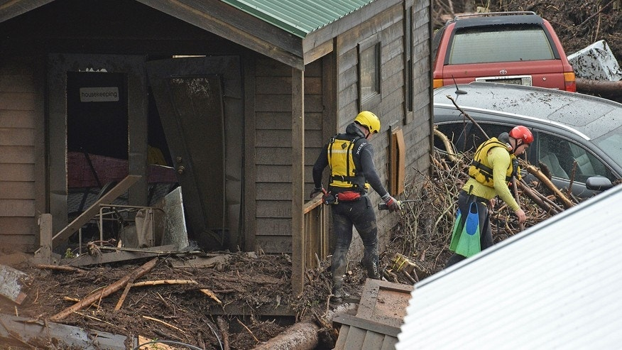 Rescue crews search for victims Friday, Jan. 20, 2017 at the El Capitan Canyon campground following flooding due to heavy rains in Gaviota, Calif. Dozens of campers were rescued and evacuated following the morning flood that swept large wooden cabins and vehicles away. (Mike Eliason/Santa Barbara County Fire Department via AP)