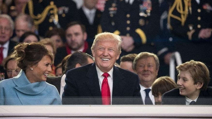 President Donald Trump shares a laugh with first lady Melania Trump and son Barron Trump as they sit in the reviewing stand during Trump's inaugural parade on Pennsylvania Ave. outside the White House in Washington, Friday, Jan. 20, 2017. (AP Photo/Andrew Harnik)