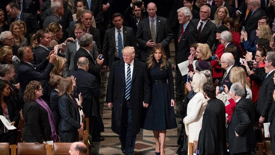 President Donald Trump, accompanied by first lady Melania Trump, arrive for a National Prayer Service at the National Cathedral, in Washington, Saturday, Jan. 21, 2017.  Trump opened his first full day as president Saturday at a national prayer service, the final piece of transition business for the nation's new chief executive before a promised full-on shift into governing. (AP Photo/Andrew Harnik)