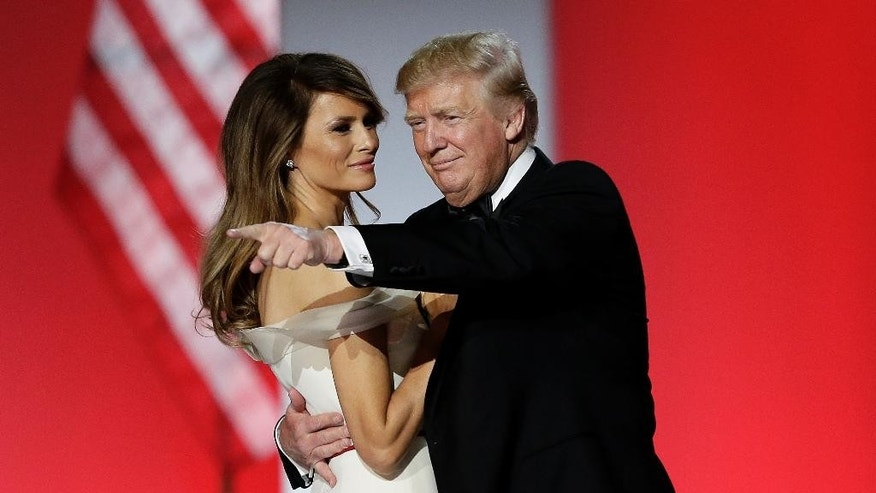 President Donald Trump points to the crowd as he and first lady Melania Trump dance at the Freedom Ball in Washington, on Friday, Jan. 20, 2017, at the Washington Convention Center during the 58th presidential inauguration (AP Photo/Mark Tenally)