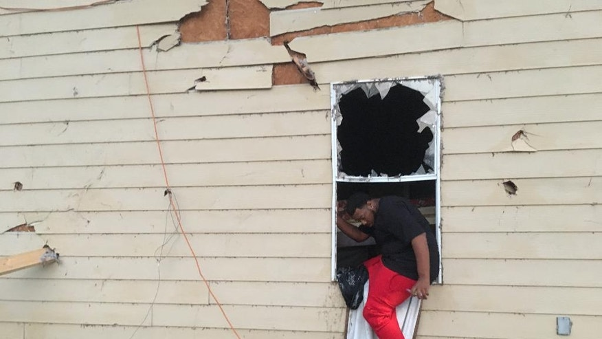 Cody Poole climbs out of a window in his family's severely damaged home in Petal, Mississippi, after looking for clothing. Poole says that's also how he and family members exited the home following a predawn tornado on Saturday, Jan., 21, 2017. Petal Mayor Hal Marx says more than 300 homes were damaged in his 10,000-resident city, along with hundreds more in its larger neighbor of Hattiesburg. The twister plowed a 25-mile path across south Mississippi, killing four people and injuring dozens. (AP Photo/Jeff Amy)
