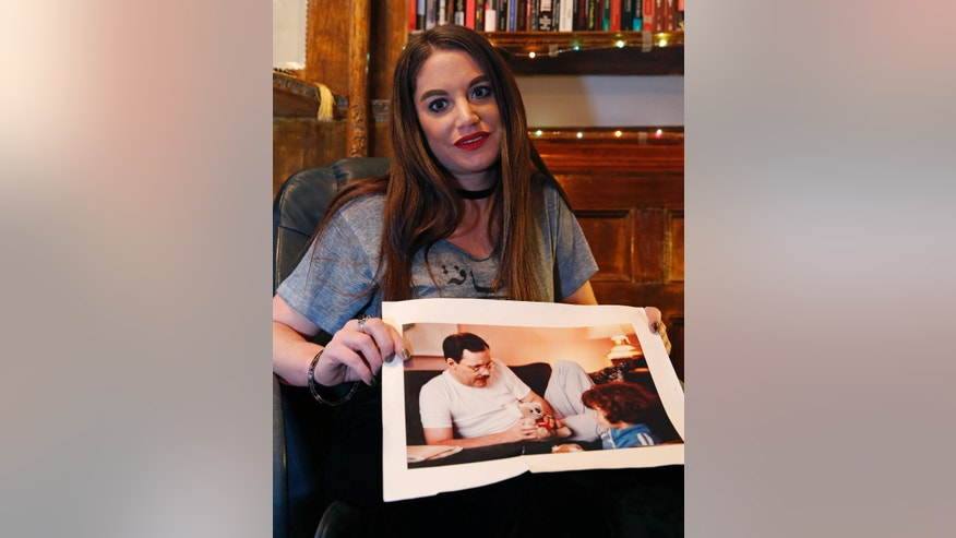 "In this Jan. 18, 2017 photo, Sulome Anderson, journalist and daughter of former American hostage Terry Anderson, holds a photograph of herself, lower right, with her father shortly after his return from Lebanon at her home in New York. Sulome said a multi-year retracing of her father's harrowing ordeal repaired their tattered relationship. Sulome describes the quest in ""The Hostage's Daughter,"" a recently published book. Her effort to research the 1985 kidnapping of Terry Anderson in Beirut, Lebanon, eventually brought her face-to-face with one of his captors. Ultimately, it led her to see eye-to-eye with her father again. (AP Photo/Kathy Willens)"