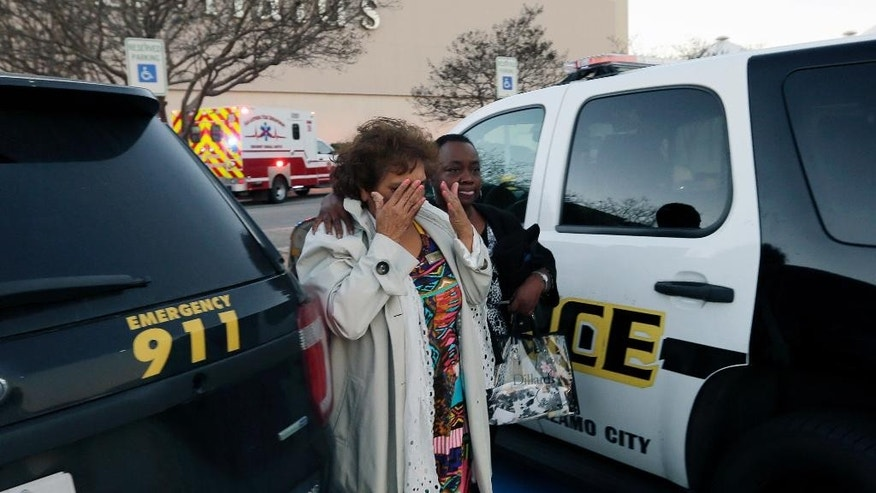 People exit the Rolling Oaks Mall, Sunday, Jan. 22, 2017, in San Antonio, after a deadly shooting. Authorities say several were injured after a robbery at the shopping mall. (AP Photo/Eric Gay)