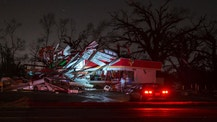 People stop to take a photo of a gas station damaged by an apparent tornado, Sunday, Jan. 22, 2017, in Albany, Ga. Nathan Deal declared a state of emergency in several counties, including Cook, that have suffered deaths, injuries and severe damage from weekend storms. (AP Photo/Branden Camp)