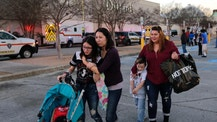 Shoppers with their children react after San Antonio police helped them exit the Rolling Oaks Mall after a deadly shooting Sunday, Jan. 22, 2017, in San Antonio. Authorities say several were injured after a robbery at the shopping mall. (AP Photo/Eric Gay)