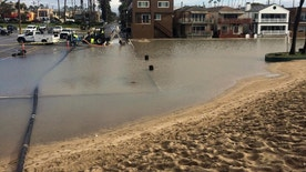 Floodwater is pumped out over a sand berm and toward the ocean in Seal Beach, Calif., on Monday, Jan. 23, 2017. The tail end of a punishing winter storm system lashed California with thunderstorms and severe winds Monday after breaking rainfall records, washing out roads and whipping up enormous waves. (AP Photo/Amy Taxin)