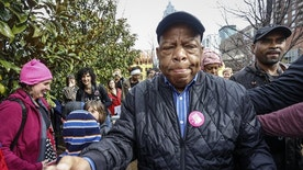 """U.S. Rep. John Lewis reaches out to shake the hands of well-wishers as he arrives at the Women's March on Saturday, Jan. 21, 2017, in Atlanta. The rally and march drew thousands of attendees, including , U.S. Rep. John Lewis, who had been at odds with president Donald Trump leading up to the inauguration. At the rally, Lewis told The AP, """"We've made progress, but there are forces in America that want to take us back to another time and another place."""" (AP Photo/Ron Harris)"""