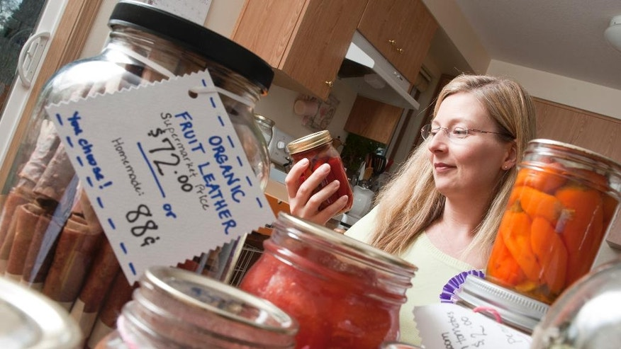 This photograph taken in a kitchen setting in Medford, Oregon, shows Master Food Preserver Michele Pryse teaching Oregon State University Extension clients safe canning techniques. The 398 volunteers in Oregon State's Master Food Preservers program donated an estimated 21,250 hours of service to their communities in 2016. Research-based training elevates volunteers into community stewards. (Lynn Ketchum/Oregon State University via AP)